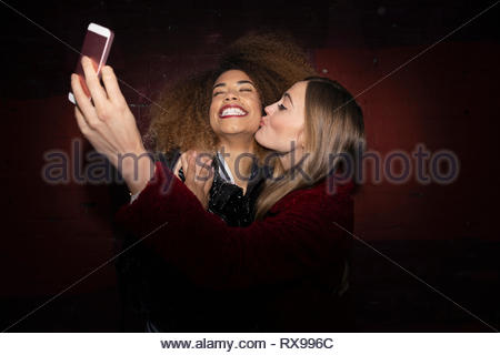Playful, affectionate women friends taking selfie - Stock Photo