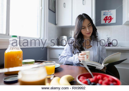 Young Latinx woman reading book and drinking coffee in morning kitchen - Stock Photo