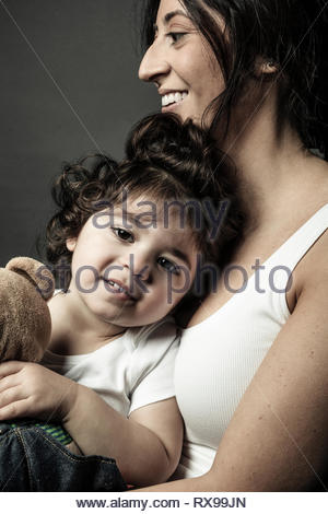 Portrait Latina mother holding cute toddler daughter - Stock Photo