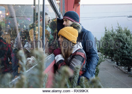 Curious couple looking in window of christmas market - Stock Photo