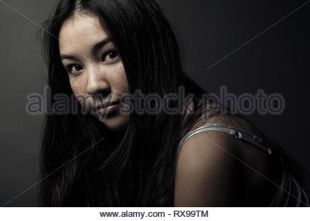 Portrait confident beautiful brunette teenage girl with long black hair and freckles - Stock Photo