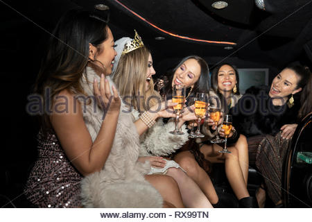 Bachelorette and friends drinking champagne in limousine - Stock Photo