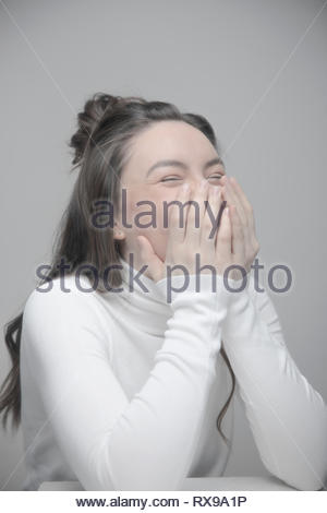 Portrait playful beautiful young woman laughing with head in hands - Stock Photo