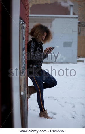 Young woman using smart phone on snowy street - Stock Photo