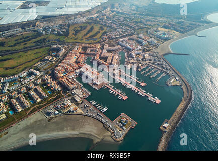 Aerial drone point view panorama of Almerimar townscape, greenhouses,  moored nautical vessels in the harbor, coastline sandy beach, Spain