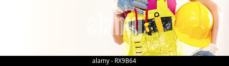 Cropped horizontal image female construction worker wearing yellow coverall holding protective hardhat posing over beige white background copy space f - Stock Photo