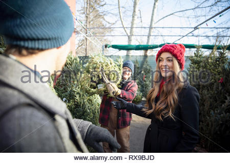 Happy couple choosing christmas tree at christmas market - Stock Photo