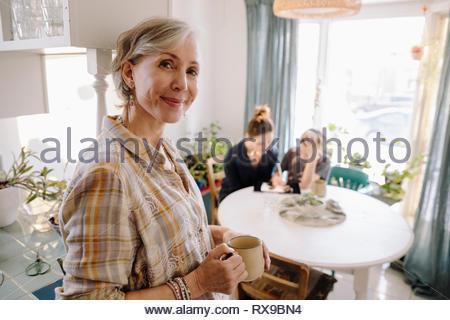 Portrait confident senior woman drinking coffee in kitchen - Stock Photo