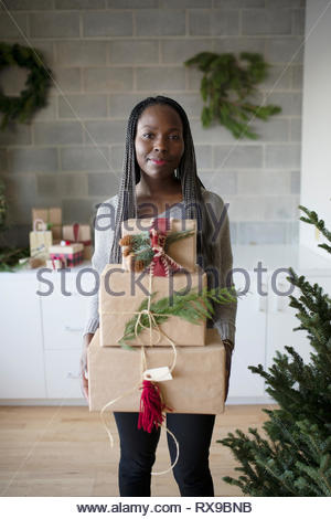 Portrait smiling young woman carrying stack of christmas gifts - Stock Photo