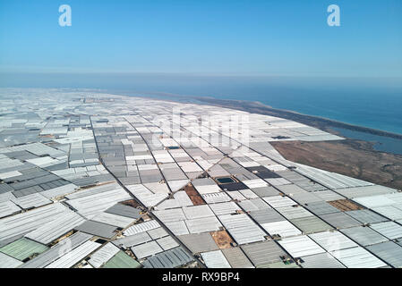 Aerial drone point of view lot of polythene plastic exterior greenhouses hothouses where cultivated fruits and vegetables in Almerimar near the sea, p - Stock Photo