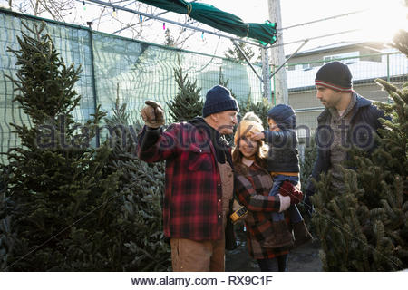 Worker helping family shopping for christmas tree at christmas market - Stock Photo