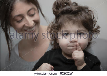 Portrait cute Latina baby girl with mother - Stock Photo