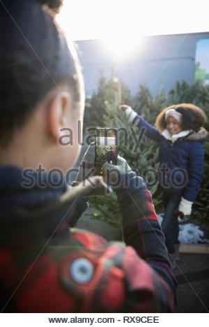 Girl with camera phone photographing sister standing next to christmas tree at christmas market - Stock Photo