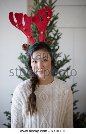 Portrait confident beautiful teenage girl wearing christmas reindeer antlers - Stock Photo