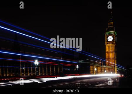 Light trails on Westminster Bridge against sky at night