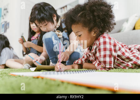 Group of little preschool kids drawing paper with color pencils . portrait of African girl with friends education concept.