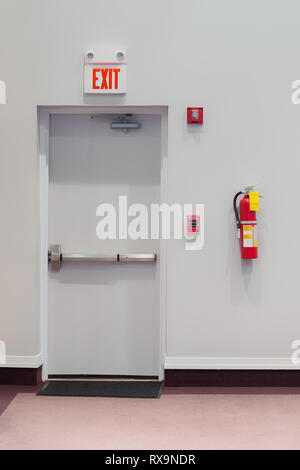 Vertical shot of an emergency exit door with a fire alarm, fire extinguisher, and an emergency light hanging on the wall next to it. - Stock Photo