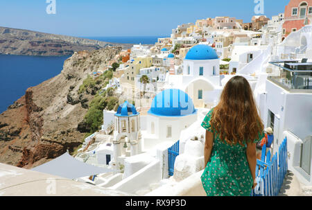 Tourist traveling in Santorini, Oia island in Greece, Europe travel summer vacation girl relaxing at view of three blue domes church famous attraction - Stock Photo