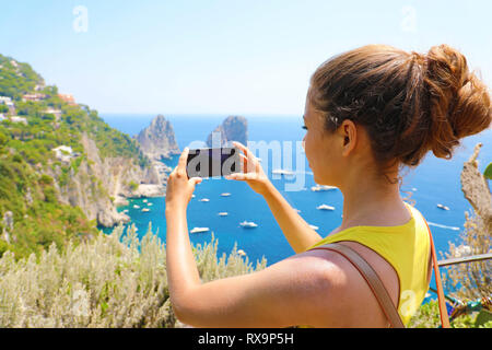 Holidays in Italy! Beautiful young woman take picture with smart phone of Capri Island, Italy - Stock Photo
