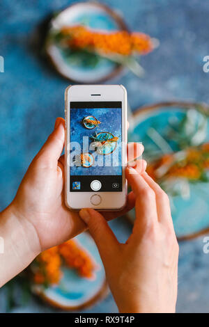 Cropped hands of woman photographing sea buckthorn berries with plates on table - Stock Photo
