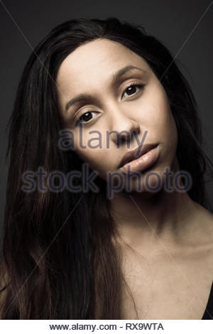 Portrait confident beautiful young Jamaican woman with long black hair - Stock Photo