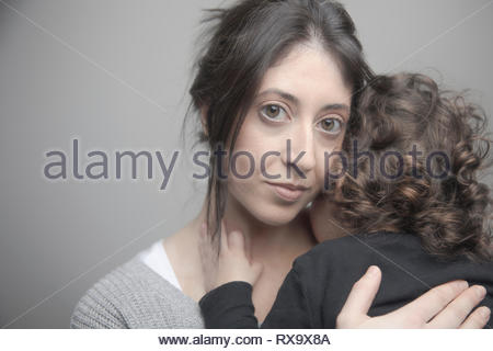 Portrait confident beautiful mother holding toddler daughter - Stock Photo
