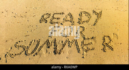 Hand written in sand ready for summer words top view - Writing in sand on beach under warm sunlight - Concept of getting ready for summer vacation - Stock Photo