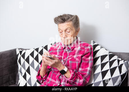 Theme old person uses technology. old gray-haired Caucasian woman with wrinkles sits home in living room on sofa and uses mobile phone in hands, looks - Stock Photo