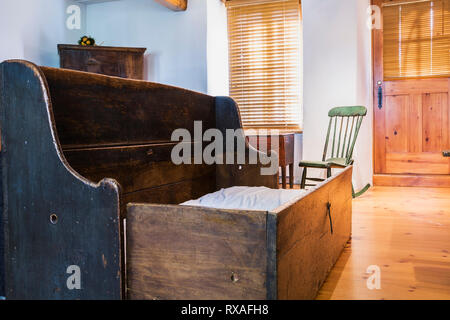 Pinewood 1830s beggar's bench and green wooden Boston rocking chair from 1880s in living room inside an old circa 1750 Canadiana style fieldstone hous - Stock Photo