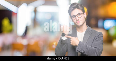Young business man wearing glasses over isolated background In hurry pointing to watch time, impatience, upset and angry for deadline delay - Stock Photo