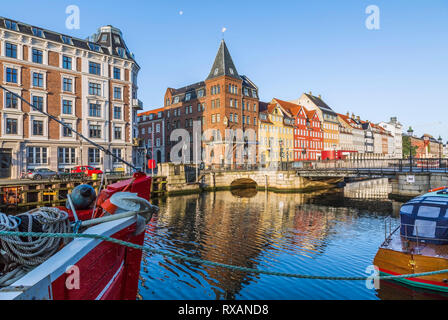 Moored boats and canal bridge with view of  Bethel aka Somandshjem hotel and colourful 17th century apartment buildings along the Nyhavn canal, Copenh - Stock Photo
