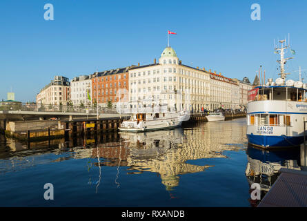 Moored yachts and blue and white Langor Helsinger spashipping ship on canal and Navigatorernes Hus Harbour Navigation building with Danish flag, Nyhav - Stock Photo