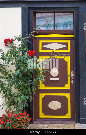 Half-timbered house facade with brown and yellow trim painted wooden front entrance door and red Rosa - Rosebush, red Begonia flowers in late summer,  - Stock Photo