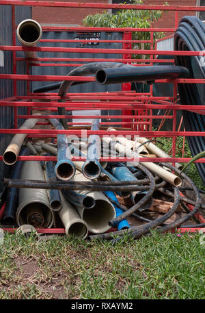 A close up view of differnt size and colour piles and cable that is staked up on red metal shelves outside on a construction site - Stock Photo