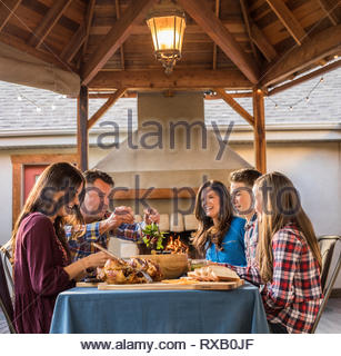 Happy family enjoying lunch while sitting in yard - Stock Photo