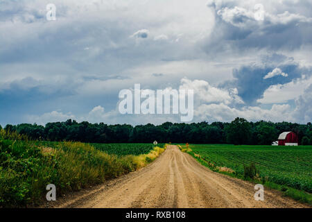 Diminishing perspective of dirt road amidst agricultural landscape against cloudy sky - Stock Photo
