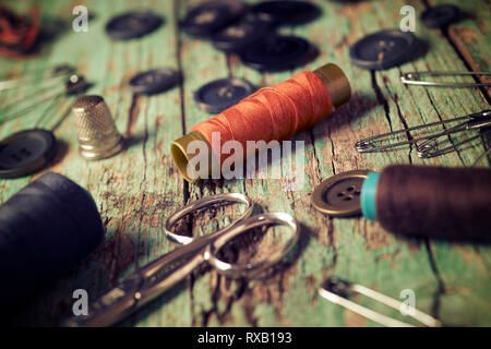 High angle close-up of various sewing items on old wooden table - Stock Photo
