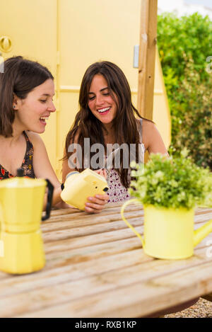 Happy female friends looking at instant print transfer at backyard - Stock Photo