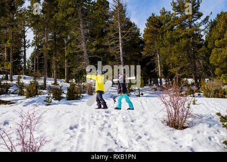 Side view of couple with snowboards walking on snow covered field in forest - Stock Photo