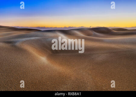 SUnrise morning sun light over lifeless untouched sand dunes in deserted area of Stockton beach in Australia - remote part of national park with rain  - Stock Photo