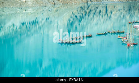 Docked boats in the turquoise Attabad lake with reflection of mountain. Gojal Hunza. Gilgit Baltistan, Pakistan. - Stock Photo