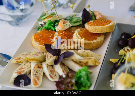 Delicious toasts with red caviar on the holiday table. - Stock Photo