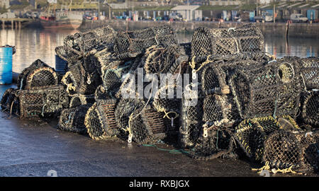 Lobster pots, piled high on Newlyn harbour quay, Cornwall, England, UK. - Stock Photo