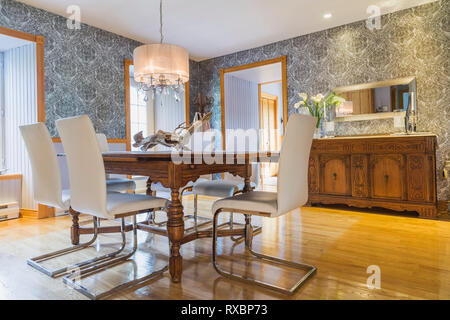 Antique oak wood table with white high back leather and chrome chairs in dining room with old wooden buffet and ash floorboards inside an old 1820 cottage style fieldstone house, Quebec, Canada. This image is property released. CUPR0332 - Stock Photo