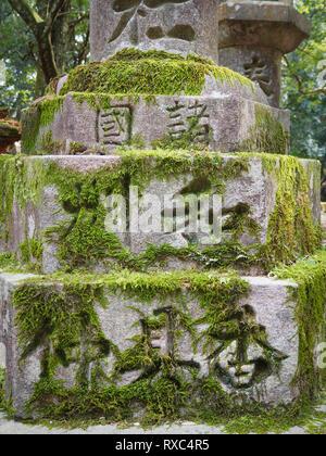 Nara, Japan - 15 Oct 2018: weathered Japanese characters on an ancient mossy stone structure near the Kasuga Grand Shrine at Nara, Japan. - Stock Photo