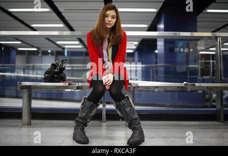 girl waiting someone who is late in the modern train platform at hong kong, china - Stock Photo