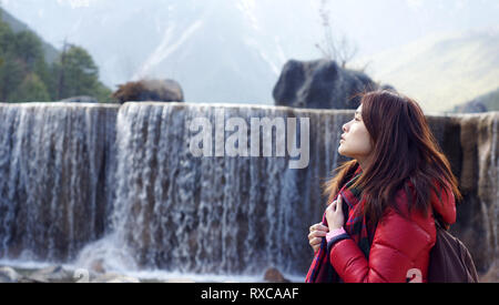 Lijiang view nature waterfall background the girl look up to the sky side view in national park - Stock Photo