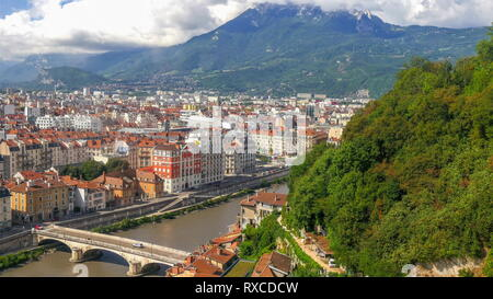 The city view of the urban city of Grenoble. The view seen from the cable car going up to the mountain alps - Stock Photo