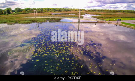 Clear waters of Tamula lake with floating leaves. The reflection of the sky can be seen on the clear waters in the lake - Stock Photo