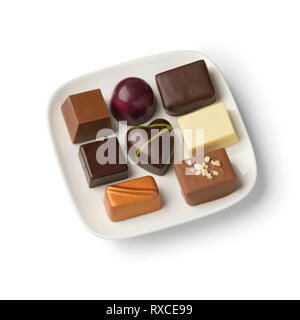 Dish with assorted chocolate bonbons isolated on white background - Stock Photo